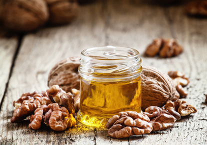 Walnut oil in a small jar and kernels on old wooden background in rustic style, selective focus
